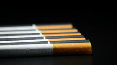 Tobacco cigarettes rotating on black background Stock Footage