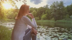 Beautiful Girl Sitting Near Lake in City Park and Dreaming 3 Stock Footage