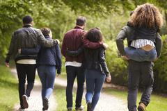 Young couples walk and piggyback in country lane, back view Stock Photos