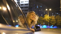 The beautiful girl outside of the window in motion of car. Evening night time Stock Footage
