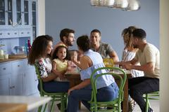 Friends with a child sit talking around a dining room table Stock Photos