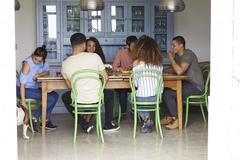 Young adult friends talk at a dining room table, full length Stock Photos