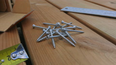Screws are being picked up from wood deck and drilled Stock Footage
