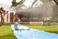 Family Having Fun On Water Slide In Garden Stock Photos