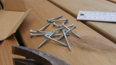 Screws are picked up and drilled. Outdoors, wood deck Stock Footage