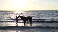 Young sexy woman dressed bikini rest with horse in the river water sunset Stock Footage