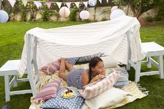 Girl Reading Book and Eating Snack In Home Made Garden Den Stock Photos