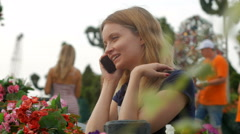 Young woman talking by phone and smiling, standing in flower bed, people walking Stock Footage
