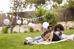 Family With Baby Relaxing On Rug In Garden Together Stock Photos