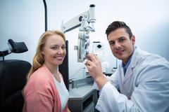 Optometrist examining female patient on phoropter Stock Photos