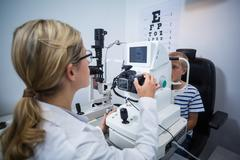 Female optometrist examining young patient on coreometry Stock Photos
