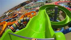 Man rides by green curvy aqua slide in water park with glass roof Stock Footage