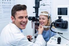 Smiling optometrist examining female patient on slit lamp Stock Photos