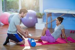 Physiotherapist assisting woman while exercising on exercise mat Stock Photos