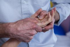 Physiotherapist giving hand massage to a patient Stock Photos