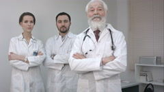 Three confident clinicians in white coats looking at camera Stock Footage