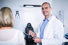 Male optometrist taking eye test of female patient Stock Photos