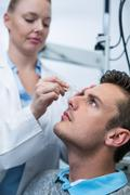 Female optometrist putting eye drop in patient eyes Stock Photos