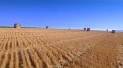Beautiful rural countryside landscape aerial shot haystacks meadow blue sky Stock Footage