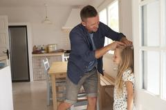 Father Measuring Daughter's Height Against Wall Stock Photos