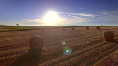 Aerial rural motion haystacks harvested field wheat straw sunlight blue sky Stock Footage