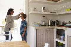Mother Measuring Son's Height Against Wall Stock Photos