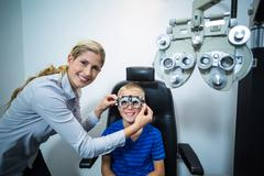 Female optometrist examining young patient with phoropter Stock Photos