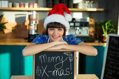 Smiling waitress wearing a santa hat and sitting with a X-mas sign board Stock Photos