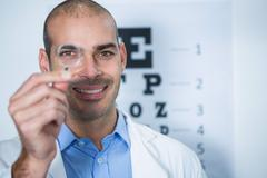 Male optometrist looking through magnifying glass Stock Photos