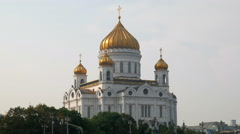 Sunset sun lying on golden domes and white walls of big orthodox church Stock Footage
