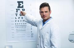 Optometrist pointing at eye chart Stock Photos