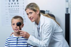 Female optometrist examining young patient with medical equipment Stock Photos
