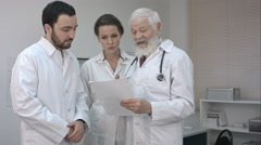 Team Of Experts Doctors Looking At Hospital Report - stock footage