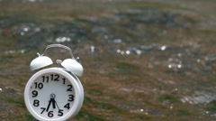 White alarm clock on waterfall background soft focus, Stock Footage