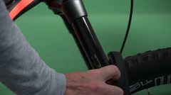 Shaking and regulation of an mountain bike fork. Green background Stock Footage