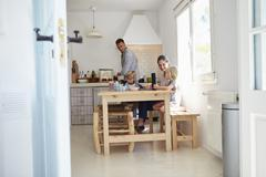 Kids at kitchen table with mum, dad cooks, view from doorway Stock Photos