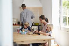 Kids and mum at table, dad cooking, three quarter length Stock Photos
