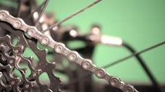 Closeup on bike chain moving with different speeds. Green background Stock Footage