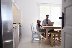 Dad and son using computers at kitchen table, from doorway Stock Photos