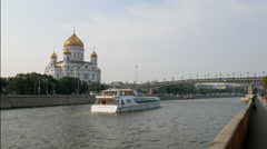 White pleasure boat floating on Moscow river to Patriarshy Bridge, near church Stock Footage