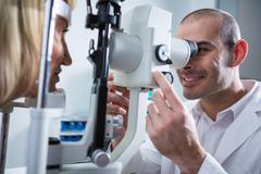 Optometrist examining female patient on slit lamp Stock Photos