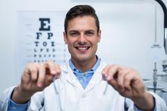 Smiling optometrist holding spectacles Stock Photos