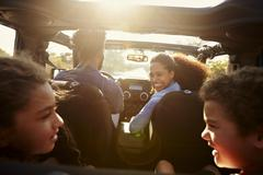Happy family on a road trip in their car, rear passenger POV Stock Photos