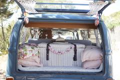 Open back of a retro camper van, with luggage and cushions Stock Photos