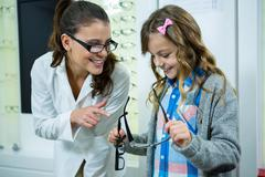 Female optometrist prescribing spectacles to young patient Stock Photos