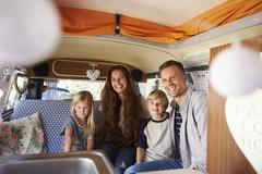 Smiling family sitting in the back of vintage camper van Kuvituskuvat