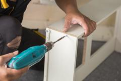 Assembling Furniture with a screwdriver Stock Photos