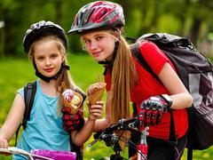 Bicycling girls with rucksack eating ice cream cone in park. - stock photo