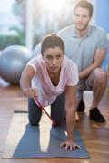 Physiotherapist assisting a female patient while exercising Stock Photos