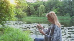 Beautiful girl using Tablet PC sitting near lake in city park 3 on sunset Stock Footage